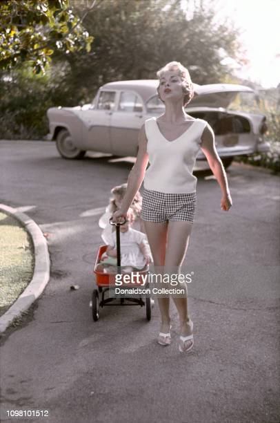 Actress Janet Leigh tows her daughters Jamie Lee and Kelly in a Radio Flyer at home on April 4, 1960 in Los Angeles, California.