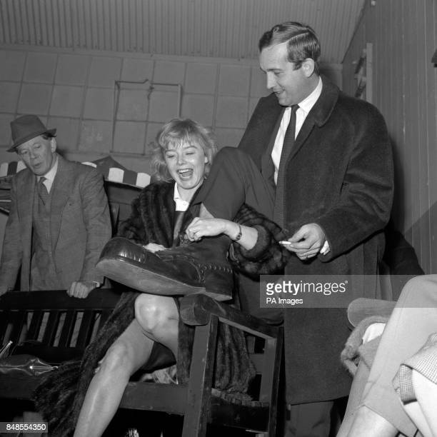 Actress Janet Munro helps her fiance actor Ian Hendry into a pair of oversized boots belonging to Coco the clown during a visit to the circus