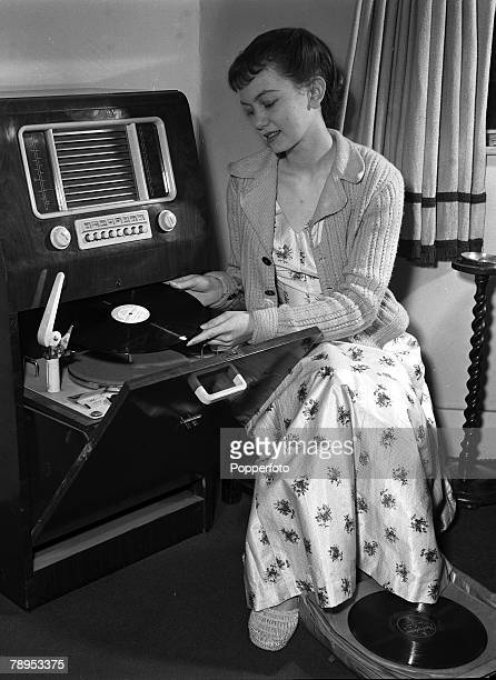 Actress Janette Scott at home in London 1954 Janette wearing a pretty flower print summer dress places a record on the turntable of a large radiogram