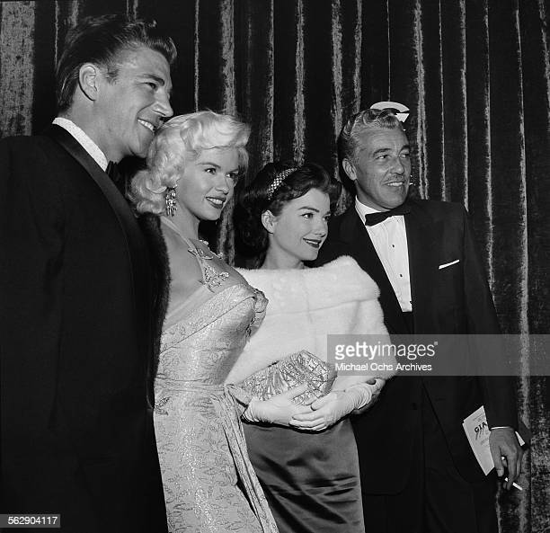 Actress Jayne Mansfield and Mickey Hargitay with actor Cesar Romero attend the premiere of 'Giant' in Los AngelesCalifornia