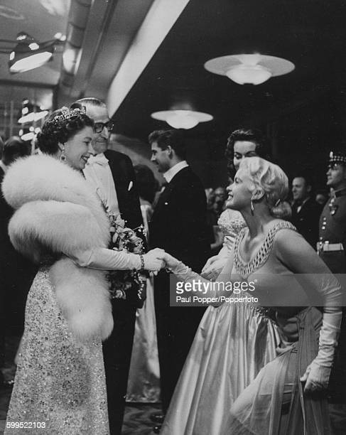 Actress Jayne Mansfield curtsying as she is introduced to Queen Elizabeth II following the Royal Command Film Performance of the film 'Les Girls' at...