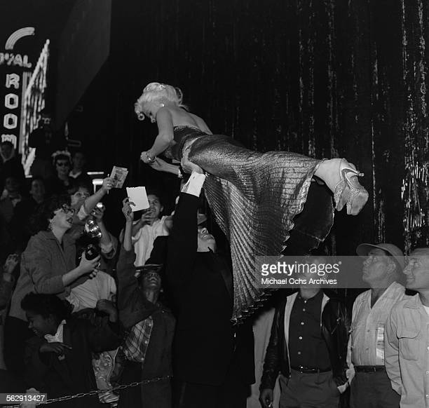 Actress Jayne Mansfield is lifted by Mickey Hargitay as she signs her autograph as they attend the premiere of Sprit of St Louis in Los...