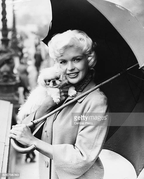 Actress Jayne Mansfield posing with her umbrella and her dog 'Powder Puff', on the set of the film 'Too Hot to Handle', Lambeth Pier, England, August...