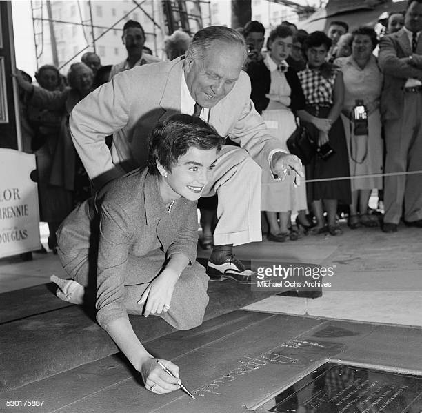 Actress Jean Simmons immortalizes her foot hand prints and hand writing at Graumen's Chinese Theatre in HollywoodCA