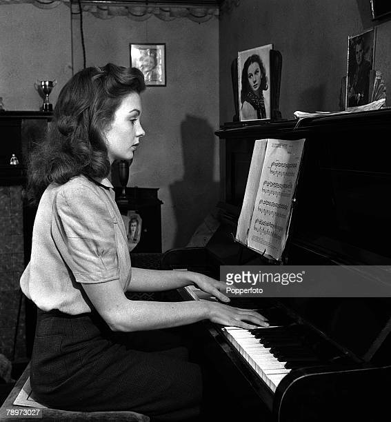 Actress Jean Simmons reading sheet music as she plays her piano at home 28th February 1946