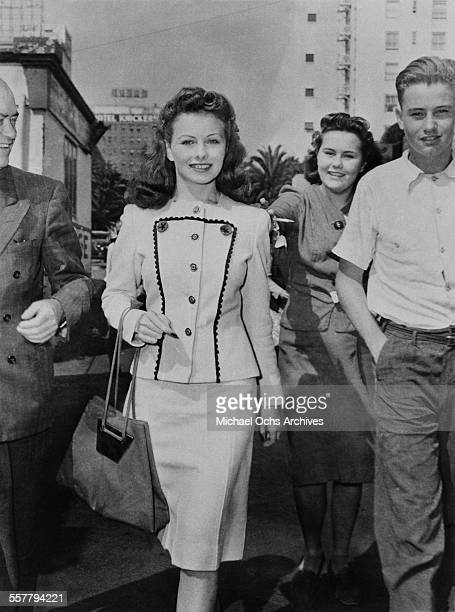 Actress Jeanne Crain walks with fans on a street in Los Angeles California