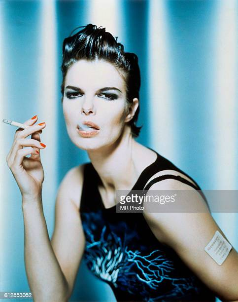Actress Jeanne Tripplehorn wears a nicotine patch while smoking a cigarette