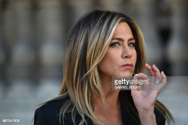 US actress Jennifer Aniston gestures as she poses during a photocall ahead of a diner for the launch of a Louis Vuitton leather goods collection in...