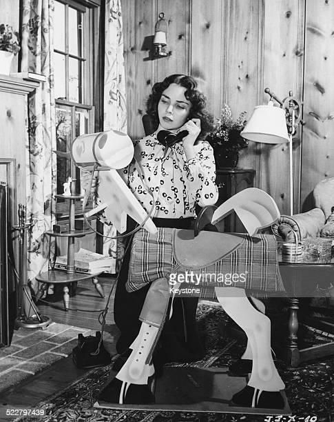 Actress Jennifer Jones working at her sewing machine in her home circa 1955