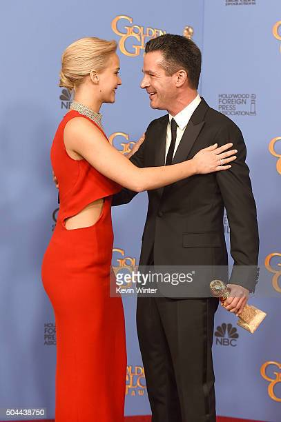 Actress Jennifer Lawrence hugs Producer Simon Kinberg winner of the award for Best Motion Picture Musical or Comedy for 'The Martian' in the press...