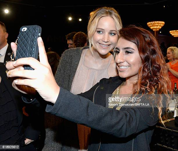 Actress Jennifer Lawrence poses with a student from George Washington Preparatory High School during the 2016 AMD British Academy Britannia Awards...