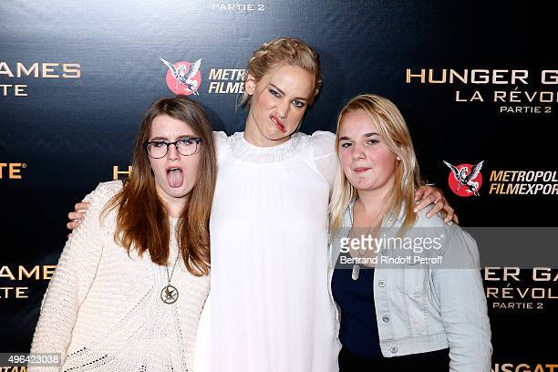 Actress Jennifer Lawrence standing between two winners of a contest to pose with her attend the 'The Hunger Games Mockingjay Part 2' Paris Premiere...