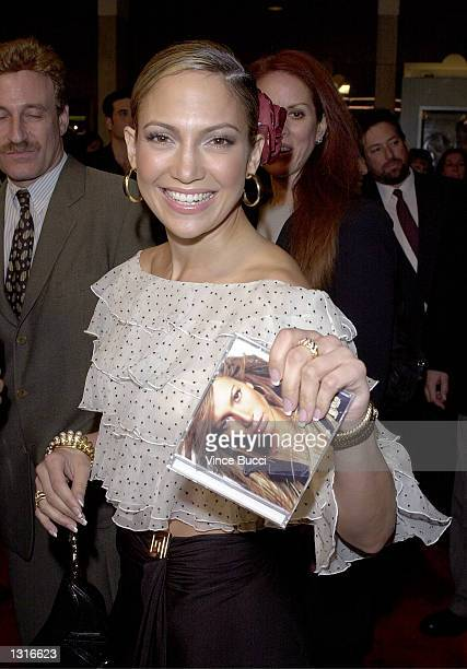 Actress Jennifer Lopez holds up her new CD as she arrives for the premiere of her new film The Wedding Planner January 23 2001 in Los Angeles CA