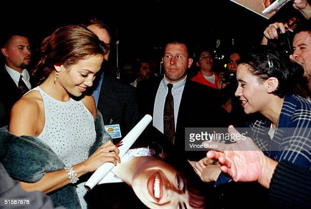 "Actress Jennifer Lopez signs a poster for fans as she arrives for the world premiere of the film ""Selena"" 13 March in Hollywood. Lopez stars in the..."