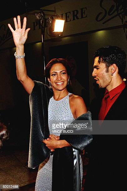 """Actress Jennifer Lopez waves to fans as she arrives with husband Ojani Noa for the world premiere of the film """"Selena"""" 13 March in Hollywood. Lopez..."""