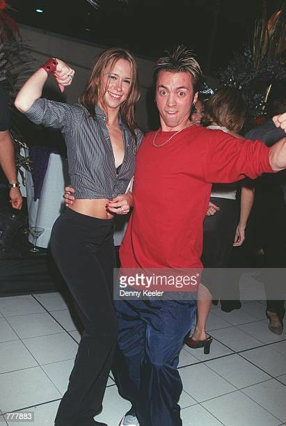 Actress Jennifer Love Hewitt flexes her muscles with Reebok guy Nate at a party for the debut of Reebok Classic Marathon Race shoe August 24 2000 in...