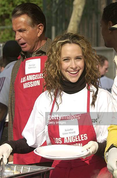 Actress Jennifer Love Hewitt right and actor George Hamilton help serve free dinners to the homeless at the Los Angeles Mission during The Great...