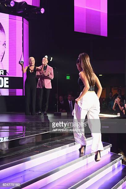 Actress Jenny McCarthy and singer Donnie Wahlberg present recording artist Ariana Grande with the award for Artist of the Year onstage at the 2016...