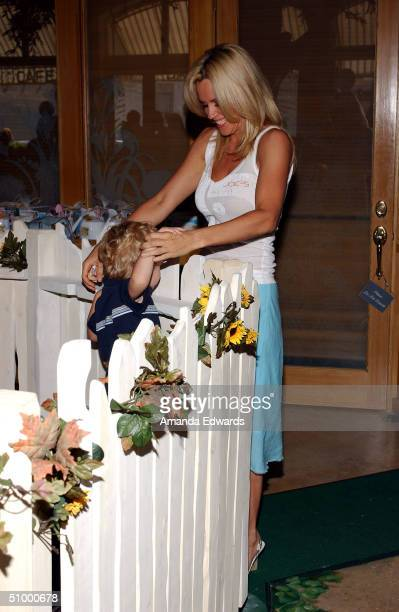 Actress Jenny McCarthy plays with her son Evan Asher poses at the opening of Nana's Garden on June 26 2004 at Nana's Garden in Los Angeles California...