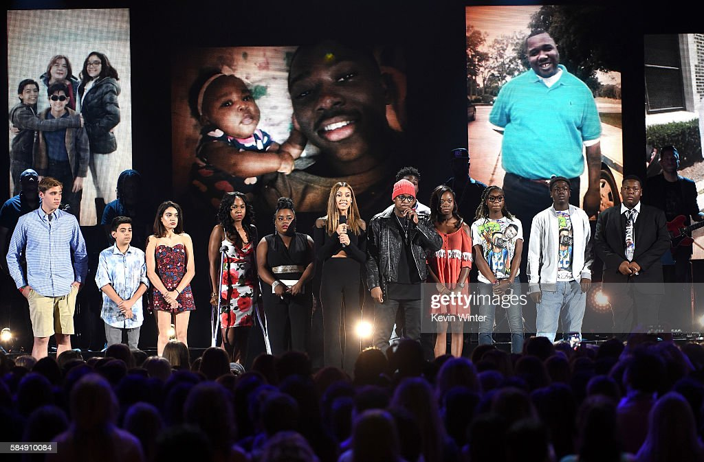 Actress Jessica Alba and recording artist Ne-Yo (C) speak out against gun violence with victims and victims' families of gun violence attacks onstage during Teen Choice Awards 2016 at The Forum on July 31, 2016 in Inglewood, California.
