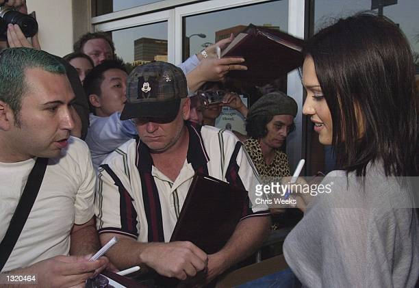 """Actress Jessica Alba signs autographs for fans while she arrives at the world premiere of Paramount Pictures'' """"Lara Croft: Tomb Raider"""" June 11 at..."""