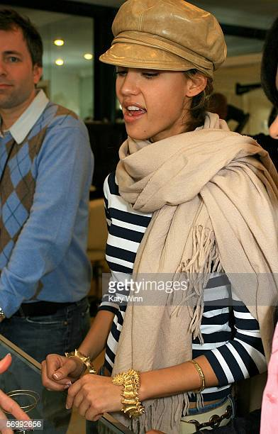 Actress Jessica Alba tries on Kristen Farrell jewelry at the REEL Lounge Retreat at the Point De Vue Salon on March 3 2006 in Los Angeles California...