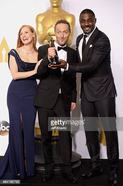 """Actress Jessica Chastain, Emmanuel Lubezki, with the award for best cinematography for """"Birdman"""", and actor Idris Elba pose in the press room during..."""