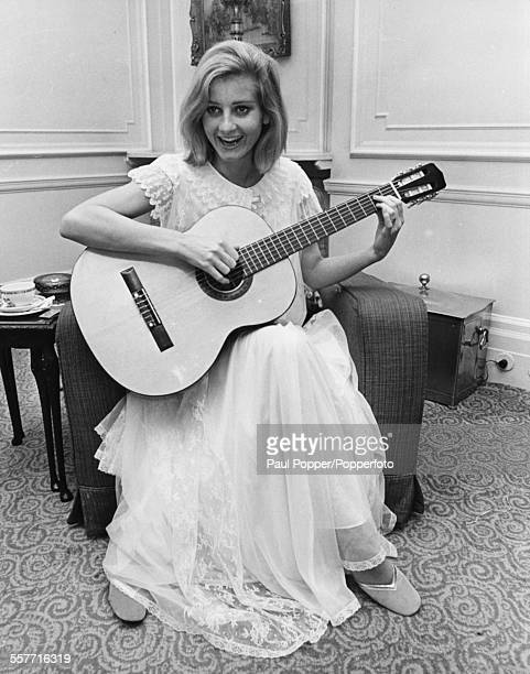 Actress Jill Ireland smiling as she practices a guitar lesson in her hotel room, London, January 10th 1969.