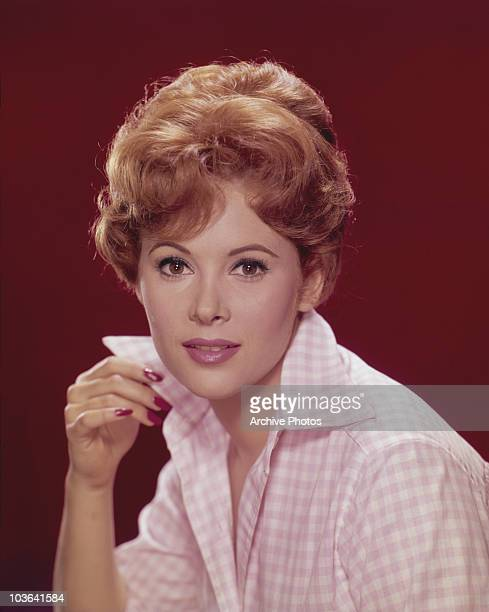 Actress Jill St John pictured with her right hand holding the collar of her pink gingham shirt USA circa 1960