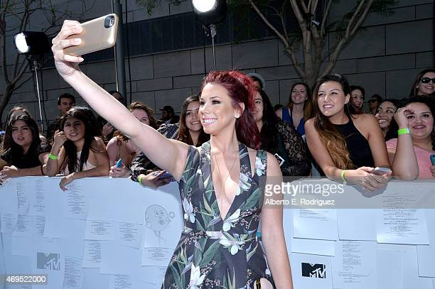 Actress Jillian Rose Reed poses for a selfie photo with fans at The 2015 MTV Movie Awards at Nokia Theatre LA Live on April 12 2015 in Los Angeles...