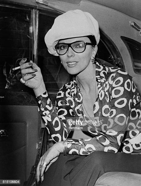 Actress Joan Collins, estranged wife of actor Anthony Newley, arrives at London Airport recently, wearing a large peak hat and a plunging neckline...