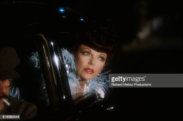Actress Joan Collins leans out of a car window. She is filming a scene from the 1986 television movie, Monte Carlo.