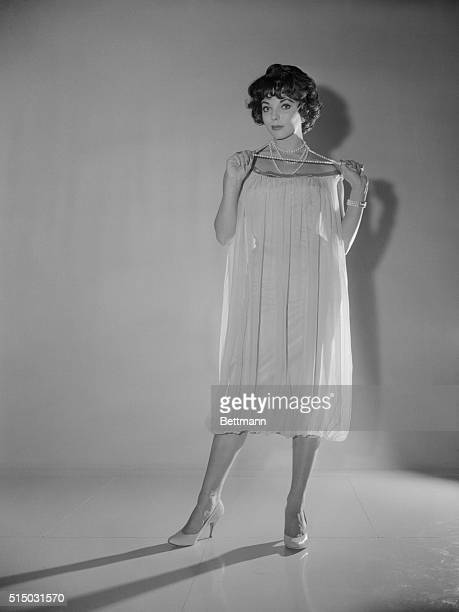 Actress Joan Collins models a sack dress she designed The dress was made by Darrell of London who makes most of Miss Collins cloths