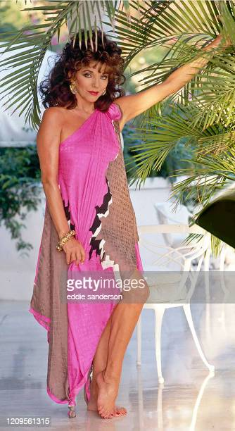 Actress Joan Collins poses on the rooftop of her villa in Acapulco, Mexico in January 2004. Joan is wearing a full length fuchsia dress with a fresh...