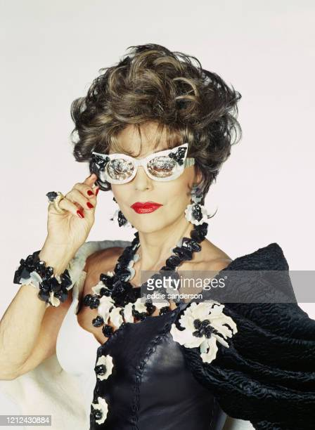Actress Joan Collins wearing a black and white leather and lace outfit with black and white cracked sunglasses and an oversized black and white...