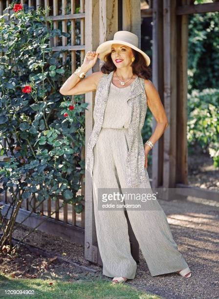 Actress Joan Collins wearing a cream and beige pant suit with wide brimmed hat in the garden of her London, England home in August 2007. .