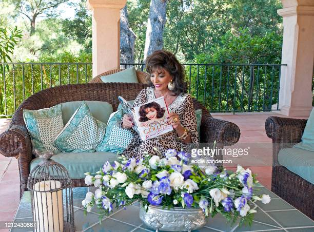 Actress Joan Collins wearing a leopard print kaftan on the patio of her Saint- Tropez villa in the South of France with her book, A Passion for Life,...