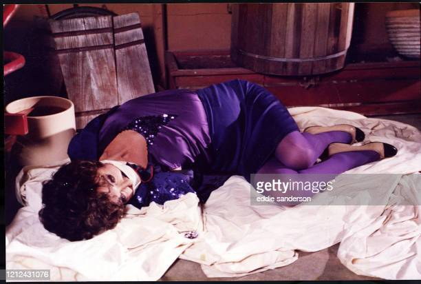 Actress Joan Collins wearing a purple dress is bound and gagged in a kidnap scene on the set of the TV show Dynasty in Hollywood California in 1987