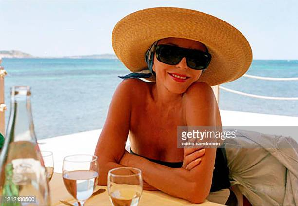 Actress Joan Collins wearing sunglasses and a wide brimmed straw hat enjoying a glass of wine at a San Tropez beachfront restaurant in the South of...