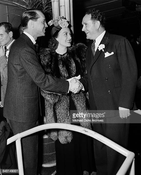 Actress Joan Crawford and husband Franchot Tone greet director Frank Borzage an event in Los Angeles California