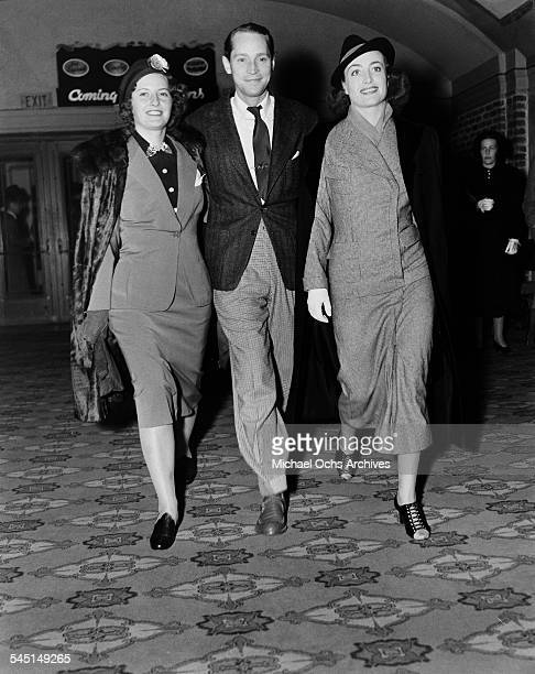 Actress Joan Crawford and husband Franchot Tone walks with actress Barbara Stanwyck to attend an event in Los Angeles California