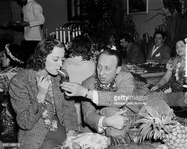Actress Joan Crawford is helped lighting her cigarette by producer Joe Pasternak during an event in Los Angeles California