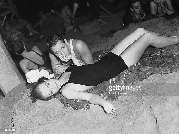 Actress Joan Crawford lounging on the beach with her costar Alan Curtis She is playing the part of Jessica Cassidy in the film 'Mannequin' directed...