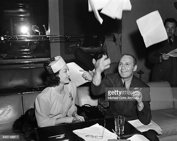 Actress Joan Crawford meets with comedian Jack Benny as he tosses papers in the air in Los Angeles California