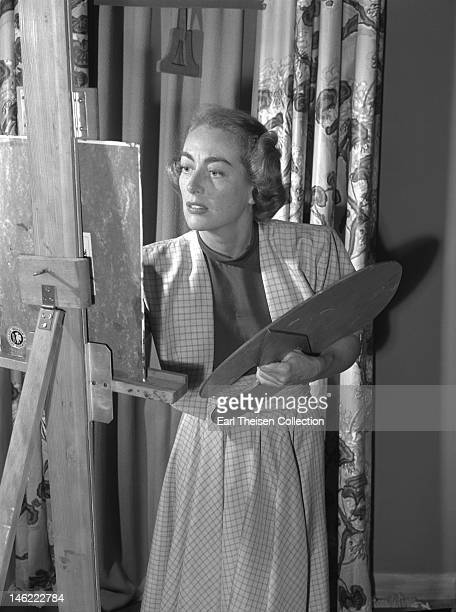 Actress Joan Crawford poses for a portrait while painting at home on July 28 1948 in Los Angeles California