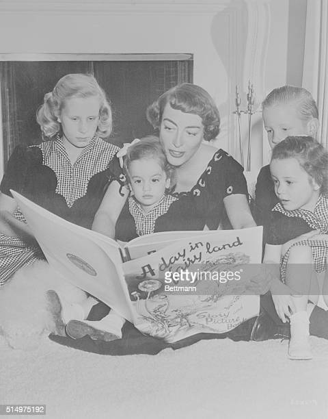 Actress Joan Crawford reads a book to her children The children are Christine Christopher Cathy and Cynthia