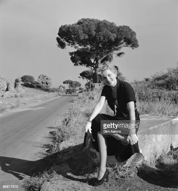 Actress Joan Fontaine massages her foot by a roadside in Italy during the location filming of 'September Affair' August 1949