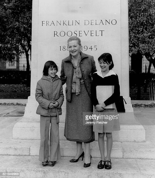 Actress Joan Fontaine poses with two children in front of the statue of US President Franklin Delano Roosevelt in Grosvenor Square London 1978