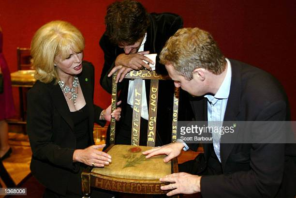 Actress Joanna Lumley Miles Apthorp and actor Rory Bremner inspect the JK Rowling 'Harry Potter' chair at the Chairish the Child celebrity auction...