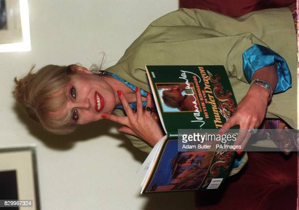 Actress Joanna Lumley poses with her book titled 'Joanna Lumley In The KIngdom of the Tunder Dragon' during a photocall in London this evening for...